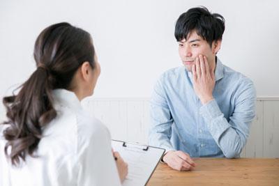 歯医者で相談する男性